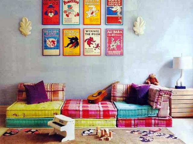 Kolorowa kanapa z poduszek, kolorowe postery na ścianie