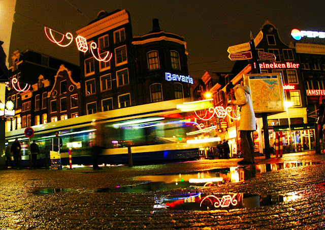 An Amsterdam train moving through the wet streets and neon signs at night.