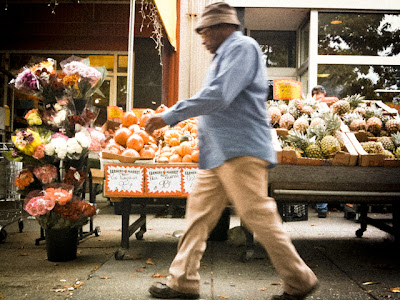 A man in a floppy hat walks past the produce stand at Magruder's Market in NW Washington, DC.