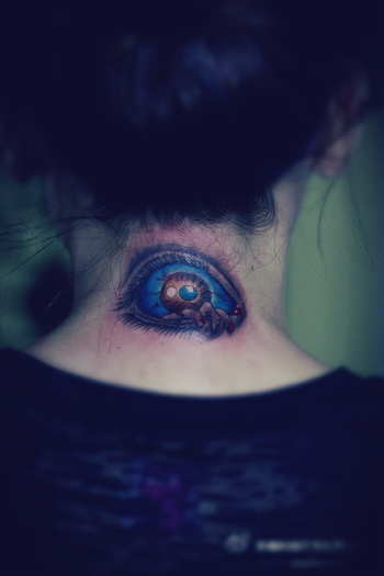 A tattoo featuring a blue eye behind the neck.