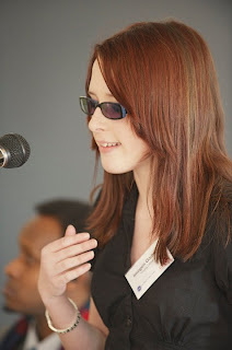 Me speaking into a microphone at a conference with shoulder length red hair, wearing a black blouse with a name tag clipped to the right. I have my hand lifted up like I am passionate about something in particular.