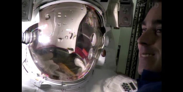 Flight Engineer Chris Cassidy checks out the spacesuit that Flight Engineer Luca Parmitano wore during a July 16 spacewalk that was cut short when water leaked into the helmet. Image Credit: NASA TV