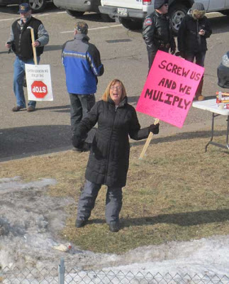 Woman with a hot pink sign reading Screw Us and We Multiply