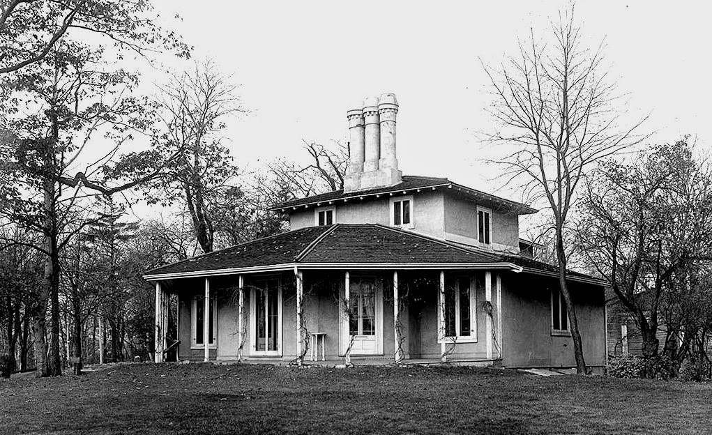 A black and white photograph of a historic house in a park setting.