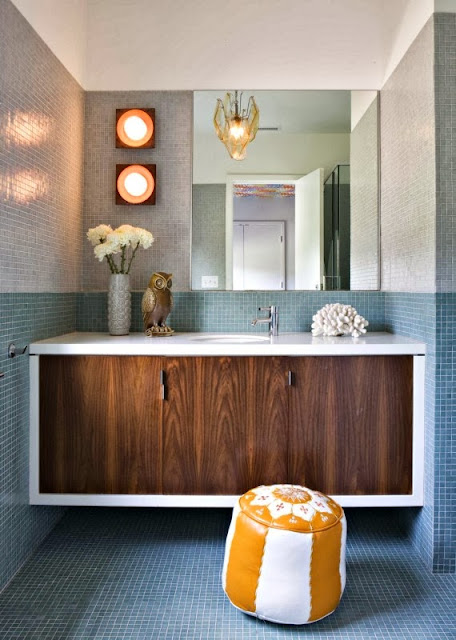 a bathroom having fun twists of unique lamp, yellow poufs, and a cute owl above the vanity