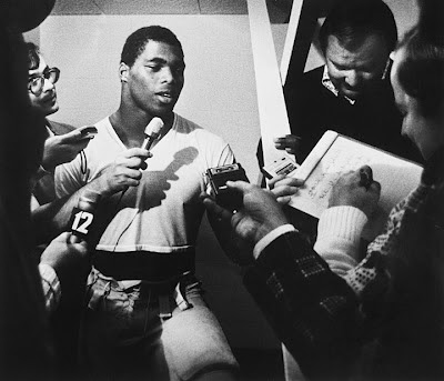Herschel Walker surrounded by reporters in the locker room