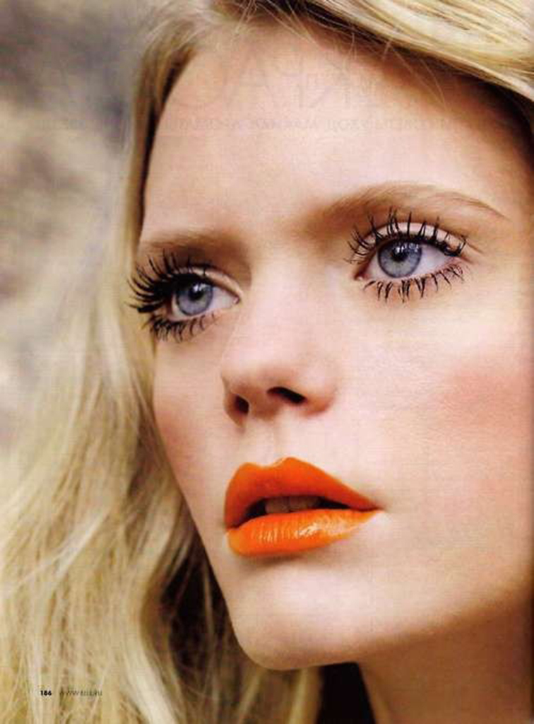 Bright orange coral lipstick, big doe eyes, perfectly separated eyelashes, blue eyes, blond honey hair