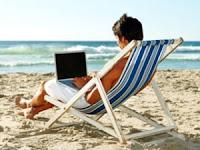 Cu laptopul pe sezlong la mare