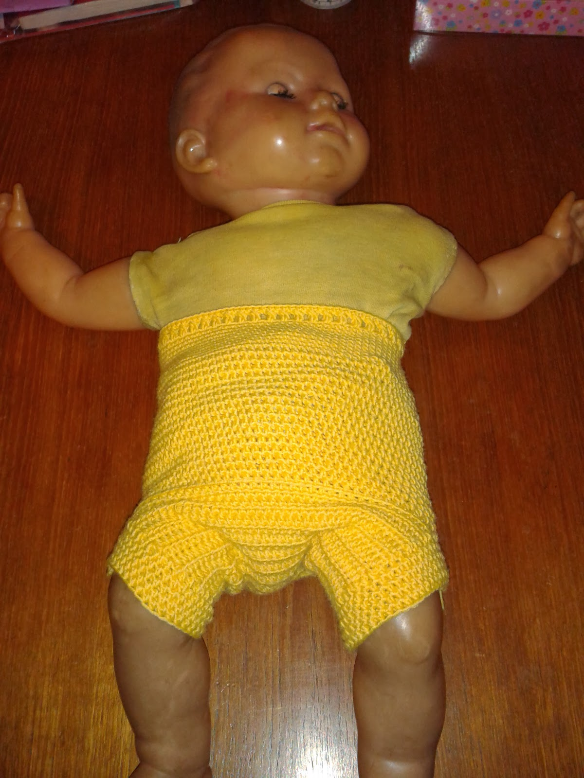 Yellow crochet nappy cover on doll