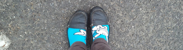 a pair of feet, their bright blue socks contrasting fiercely with black loafers and grey cement