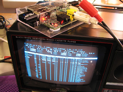 [Image: The cathode ray display showing the Linux console running the 'top' command. On top of it, a Raspberry Pi with two small devices connected into its USB ports and an RCA cable connected into its analog video output.]