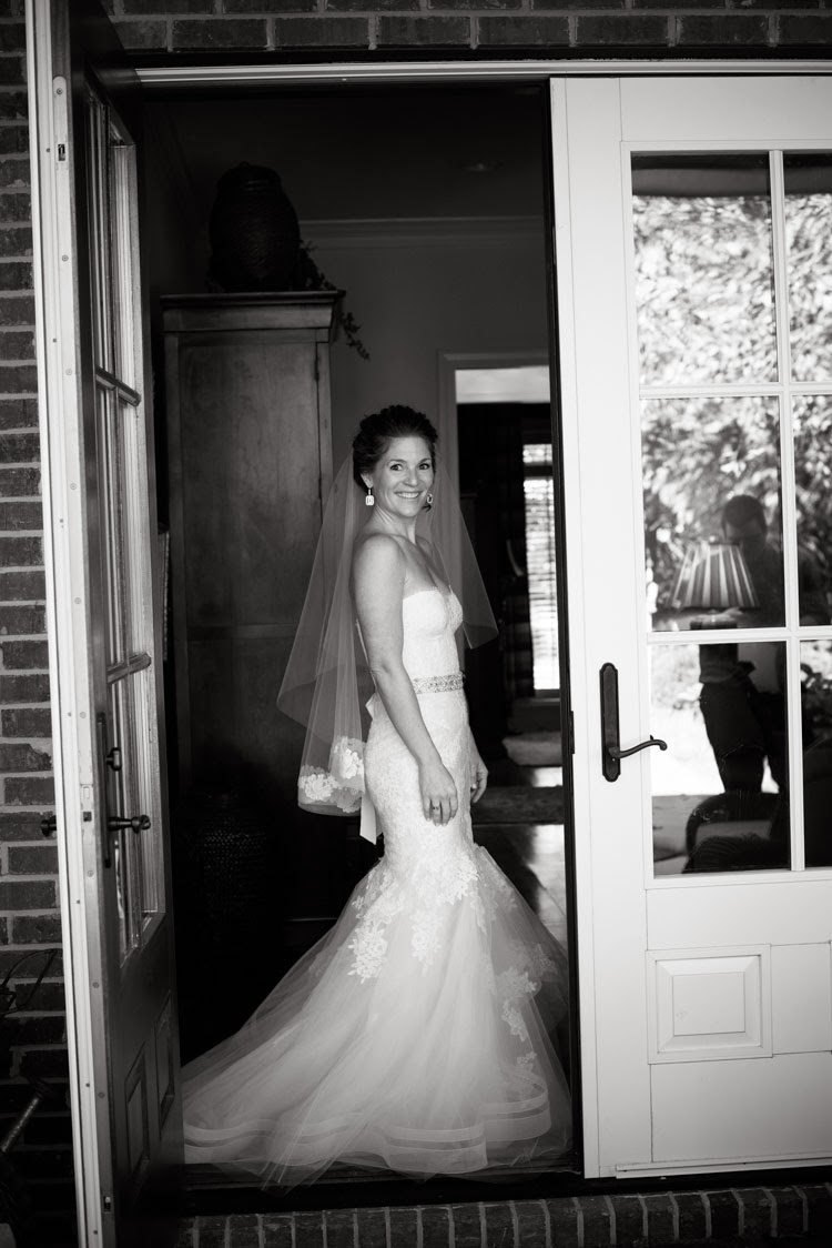 bride in doorway smiling in her Monique Lhuillier wedding dress