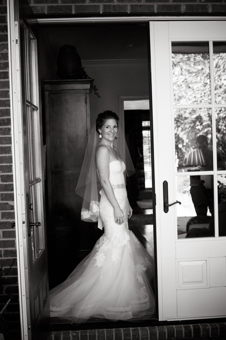 bride in doorway smiling in her Monique Lhuillier wedding dress