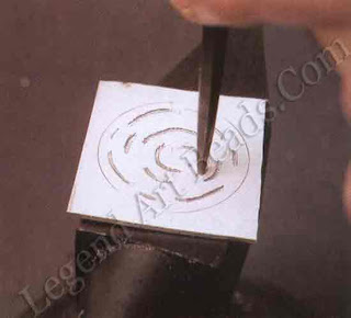 Use a punch that is no wider than the wire that is to be inlaid and, holding the punch above the work, strike it with a medium-weight hammer. Work smoothly along the lines of the design, overlapping each stroke as you make the next one.