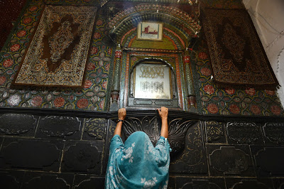 A Kashmiri Muslim woman embraces an inner wall of the 600-year-old shrine of Syed Mir Ali Hamdani, during the annual Urs in downtown Srinagar.