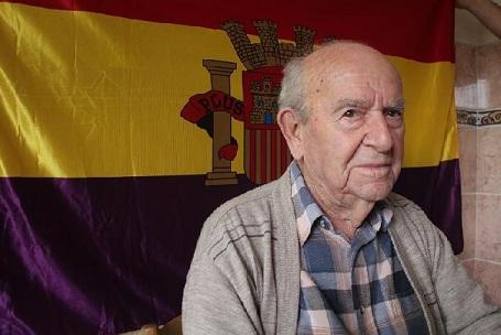 De pie y con el puño en alto el miliciano Virgilio Peña celebra su 102 cumpleaños