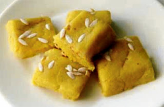 Saffron Paneer Burfi: Classic Indian Diwali sweet snack of squares of sweetened curd cheese thickened with milk powder and ground almonds flavoured and coloured with saffron and decorated with melon seeds