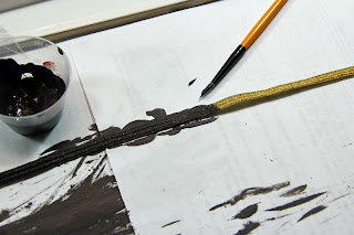 Painting the gold lace with brown textile paint.