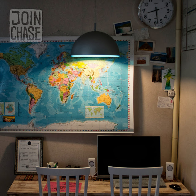 A world map on a wall with postcards and a computer at Pedro's House in Gwangju, South Korea.