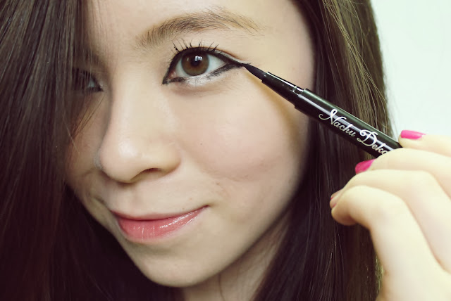 Girl applying eyeliner