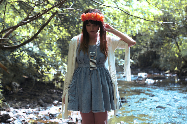 hippy girl, festival look, wearing roses and clementines floral crown in vivid orange, tassel kaftan kimono, denim pinafore topshop dress with tribal bone native american necklace with platform jeffrey campbell boots, British fashion, UK styling in the summer, how to get the hippy festival look.
