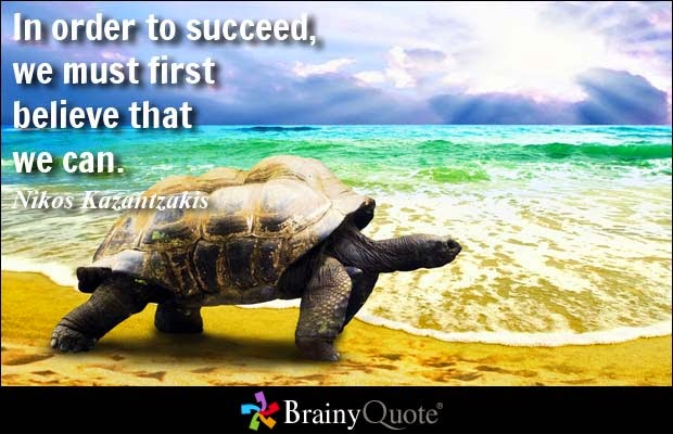"""In order to succeed, we must first believe that we can."" ~ Nikos Kazantzukis; Picture of a tortoise walking on a beach with the sun shining in the background."