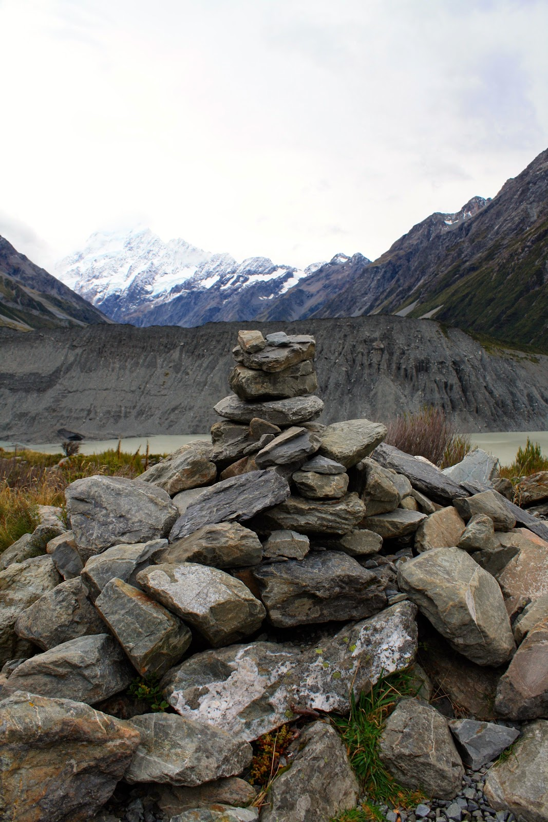 A picture of a cairn of staked rocks in front of Aoraki/Mt Cook in New Zealand's South Island.