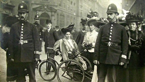 black and white photograph of Rosa May Billinghurst sitting in her adapted wheelchair after being arrested, surrounded by police officers and members of Women's Social and Political Union