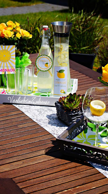 summer in the garden: decorated table with lemon candles and handmade lemonade
