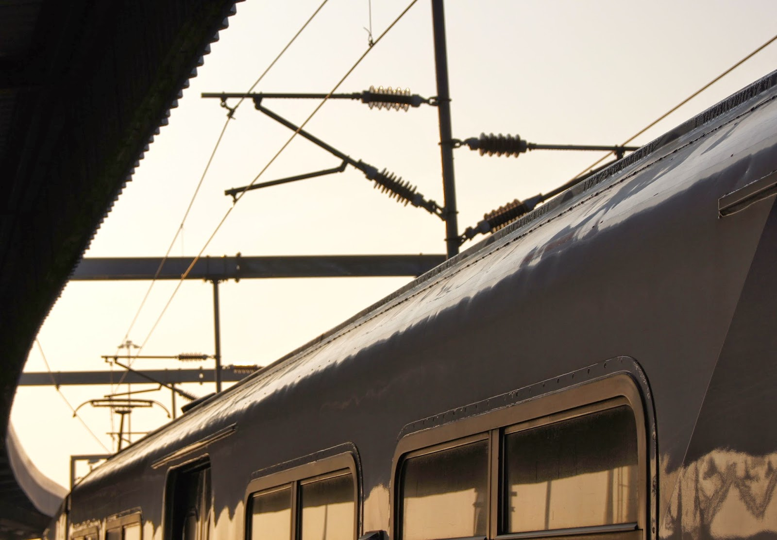 Personenzug steht am Bahnhof, die Sonne geht auf und man erkennt die Silhouette des Zuges.