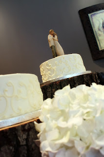 White wedding cake with swirl design on rustic tree stands