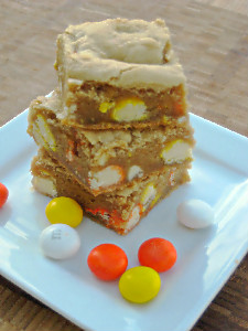 blondies stacked on a white plate with M&ms next to them