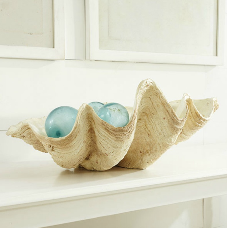 Sea glass flaots displayed in a giant clam shell
