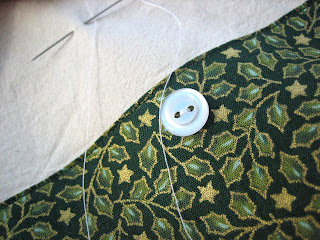Photo showing green printed fabric with a white button
