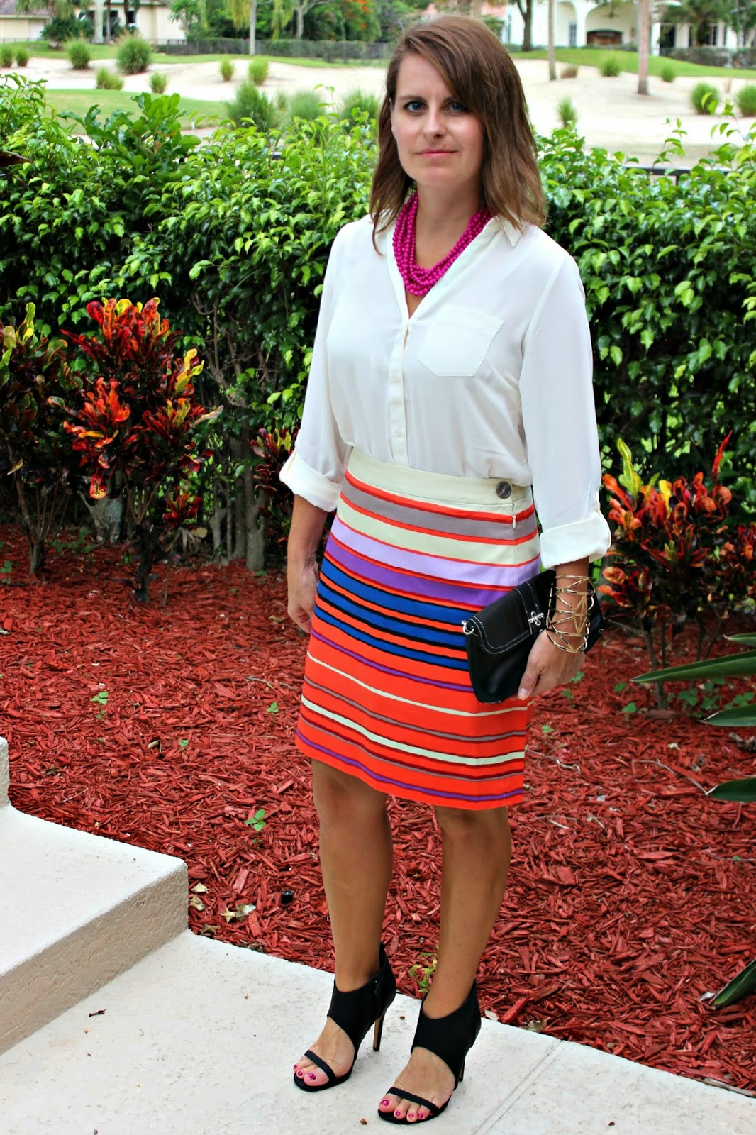 colorful striped pencil skirt, off white silky blouse, purple layered necklace, funky black heels, gold cuff