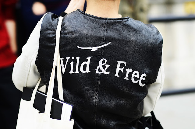 Candid street style, London, black leather jacket with white text