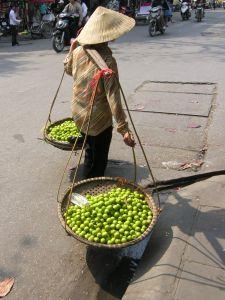 Człowiek niosący owoce na targu w Wietnamie.