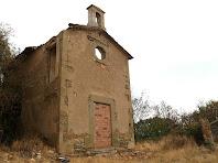 Vista lateral de la capella on s'aprecia el forat del pas que permetia accedir de la casa al cor de la capella