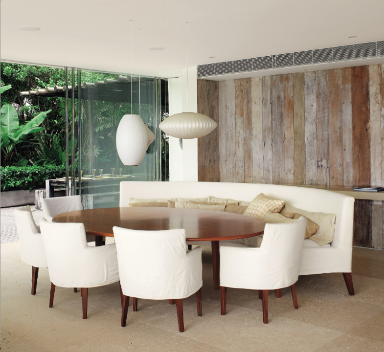 Modern dining room with a tropical garden just outside the floor to ceiling glass doors.