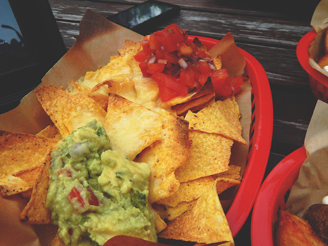 guacamole, cheese, and salsa on top of tortilla chips