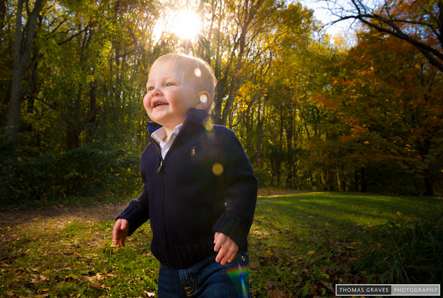 A toddler beams up at his mother, out of the frame, as he walks in a sunlit meadow.