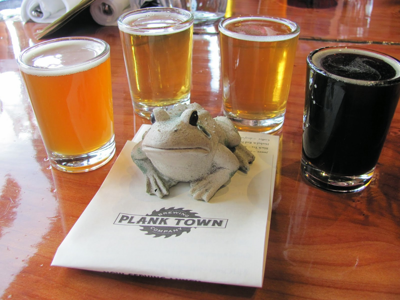 Frog poses with the flight of beverages at Plank Town Brewery in Springfield, Oregon