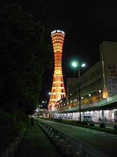 Photo of the lit up orange Kobe Port Tower from a nearby street at night