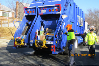Two workers with their recycling truck.