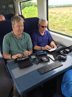 Mike and Bob on the train with their techonogy, BrailleNotes, phones, VictorReaders Stream