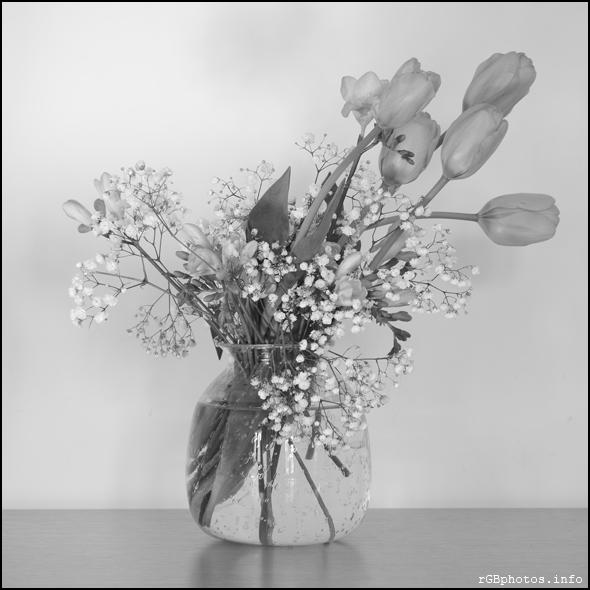 Fotografia in bianco e nero di un mazzo di fiori in vaso di vetro