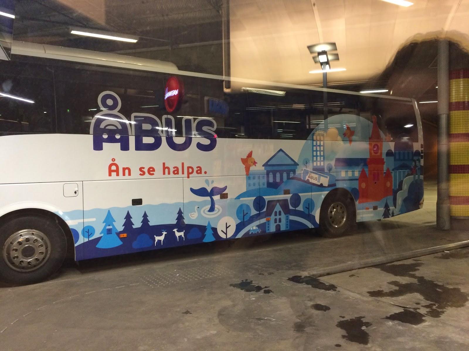 Åbussin bussi kuvattuna kampin terminaalin lasin läpi