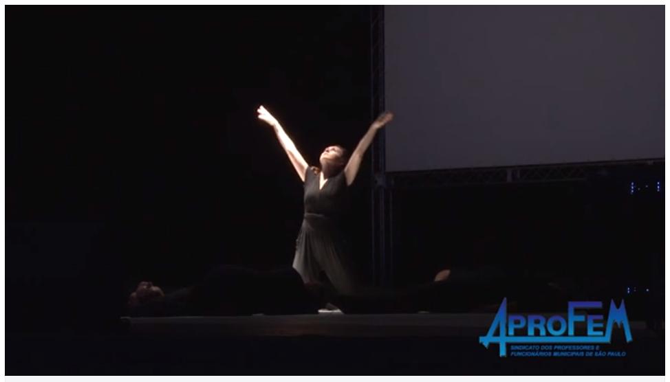 Descrição da Foto: Intérprete está ajoelhada com os braços estendidos para cima em V, com o rosto voltado para um foco de luz branca.