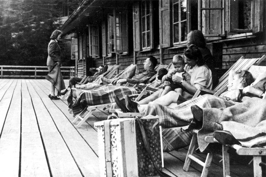 SS officers relax together with women and a baby on a deck at Solahütte. As the SS members took time off, hundreds were being exterminated nearby at Auschwitz.