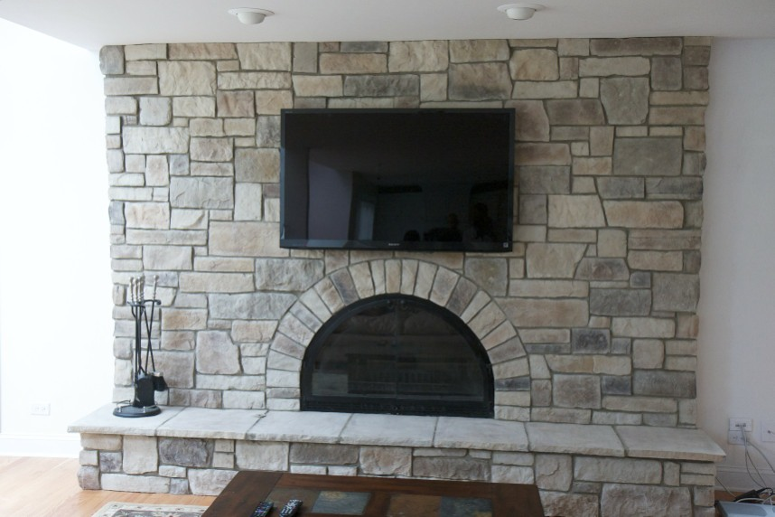 finished cobble stone fireplace tv installation over fireplace you